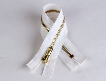 White zipper with brass gold colored teeth.
