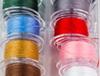 Bobbin case with pre-wound thread in different colors. thumbnail image.